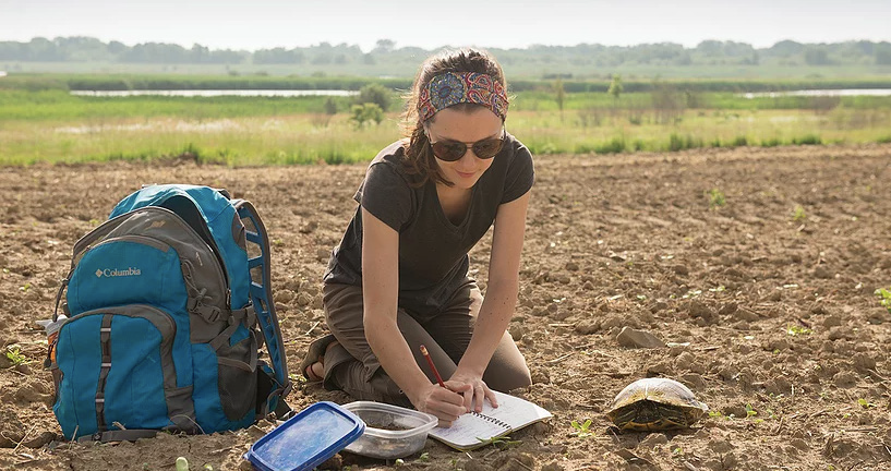 Picture of Amanda Wilson Carter. She is in a dirt field writing in her notebook. There is a turtle to her left.