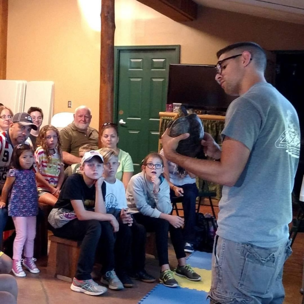 Anthony Breitenbach stands at the front of a room full of children and their parents. He holds a turtle in his hands and the children are watching intently.