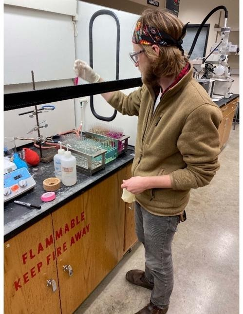 A picture of David pipetting chemicals under a fume hood.