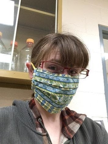 Kara wears a face mask and smiles at the camera. She is in a laboratory.