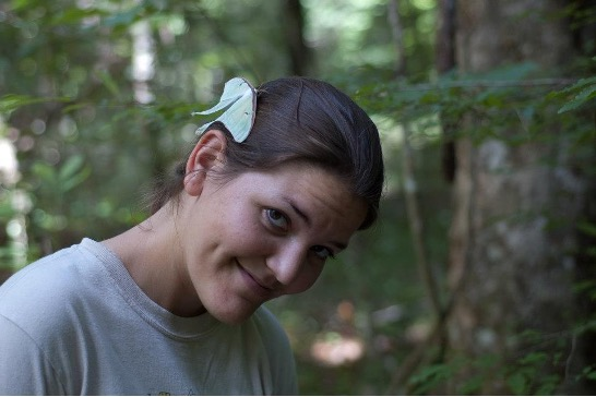 A large green Luna Moth perched on the side of Lisa's head while in the forests in the Southeastern United States. She was a graduate student at the time and was hiking through the woods, probably looking for amphibians.