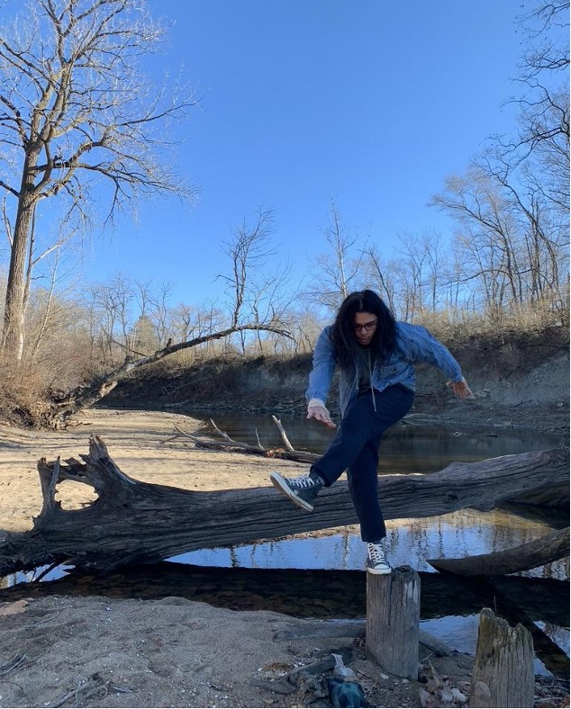 Austin posing on tree stumps at a riverbed.